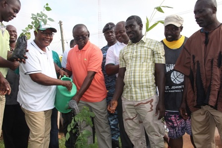 Hon. Osei Assibey Antwi (3rd left) and Nana Owusu Barima III (in cap) jointly water a newly planted seedling.