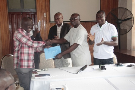 Hon. Nana Kwaku Dua (L) presenting the report to Hon. Osei Assibey Antwi (R)