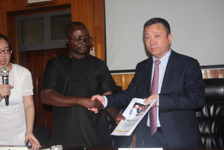 Osei Assibey Antwi on the left presenting a document on investment opportunities to Mr. Xie Shuhua , with them was an interpreter.