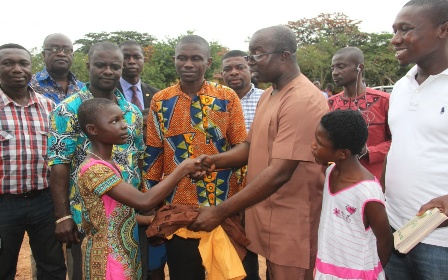 Hon. Osei Assibey Antwi, presenting school uniform to one of the pupil