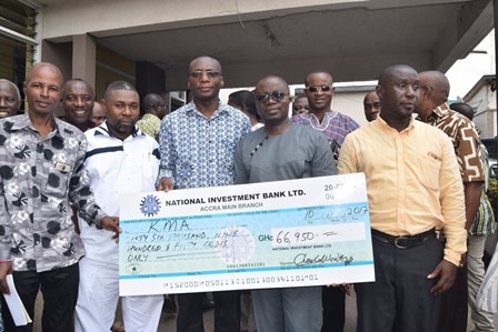 Hon. Osei Assibey Antwi (Second from right) receiving the check from Mr. Charles Wordy , with them were  some Assembly members and staff of KMA.